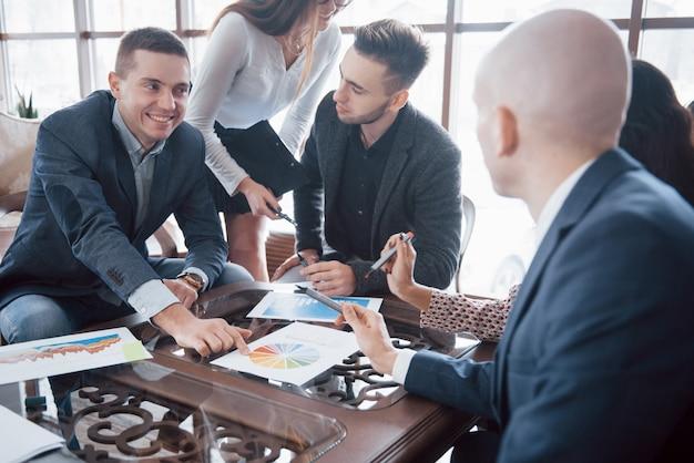Jong team van collega's maken van grote zakelijke discussie in het moderne kantoor. teamwork mensen concept