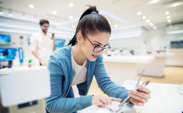 Jong tevreden stijlvolle charmante mooi meisje testen van het nieuwe model van een mobiel vanaf het bureau in de tech winkel.