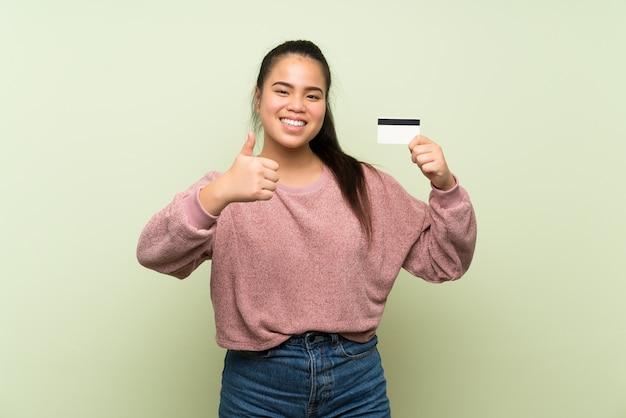 Jong tiener aziatisch meisje over geïsoleerde groene muur die een creditcard houdt