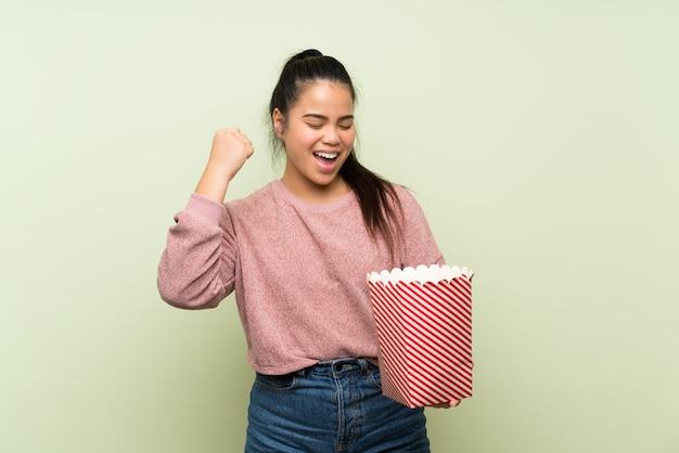 Jong tiener aziatisch meisje over geïsoleerde groene muur die een kom popcorns houdt