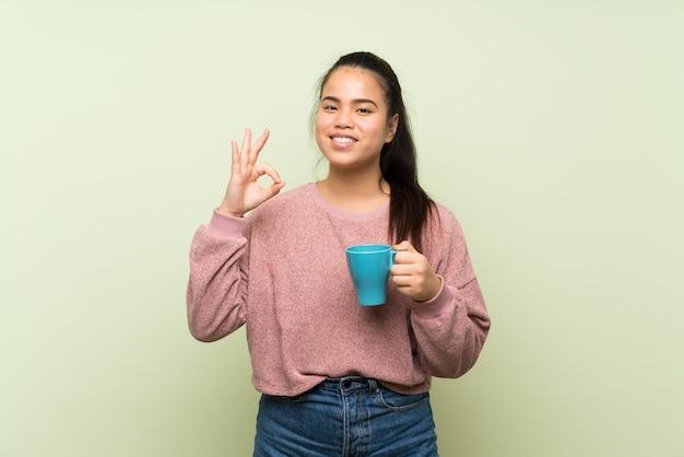 Jong tiener aziatisch meisje over geïsoleerde groene muur die hete kop van koffie houdt