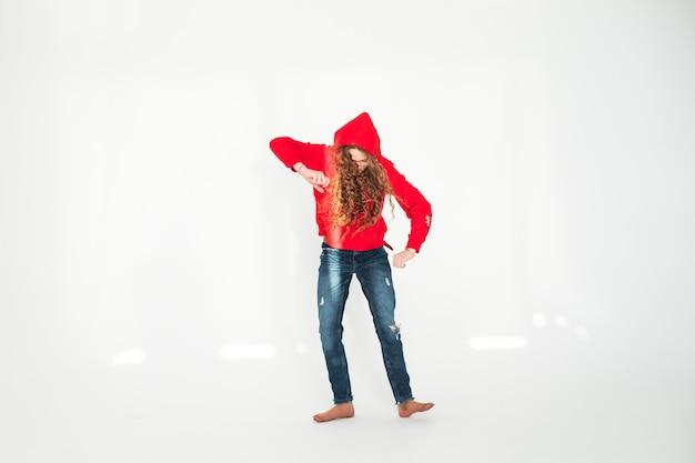Jong tienermeisje dansen in volle groei op witte achtergrond in de studio in stralen van de zon