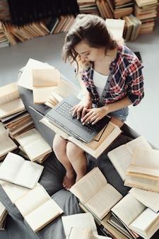 Jong tienermeisje dat de laptop computer met behulp van die door vele boeken wordt omringd.