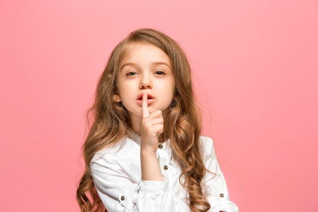 Jong tienermeisje dat een geheim achter haar hand fluistert dat op trendy roze studiomuur wordt geïsoleerd.