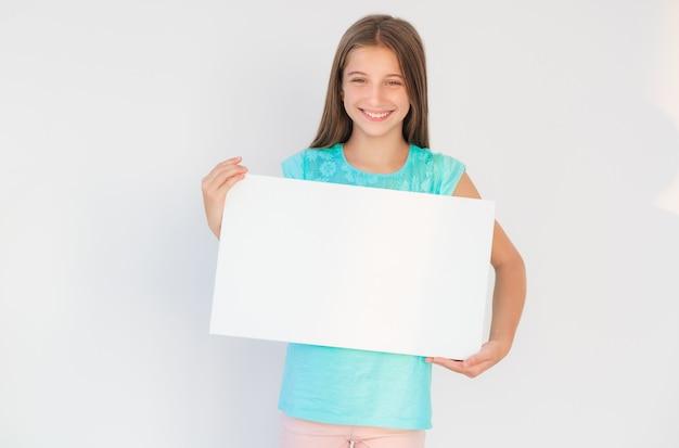 Jong tienermeisje dat een leeg aanplakbiljet houdt