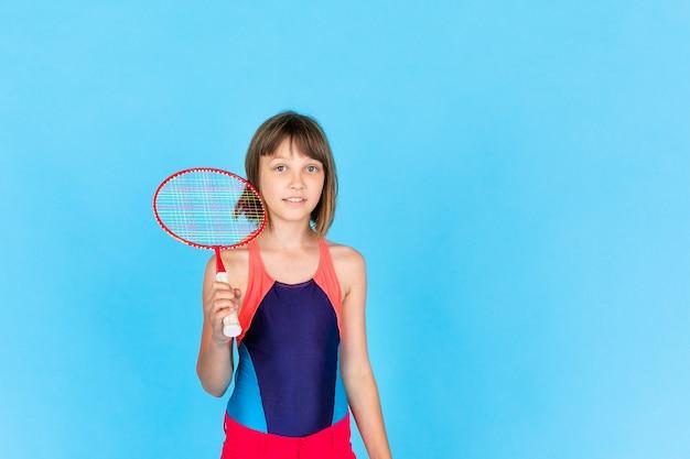 Jong tienermeisje dat en badminton op blauwe muur springt speelt