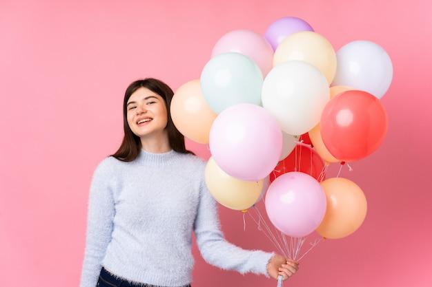 Jong tienermeisje dat veel ballons over het roze muur lachen houdt