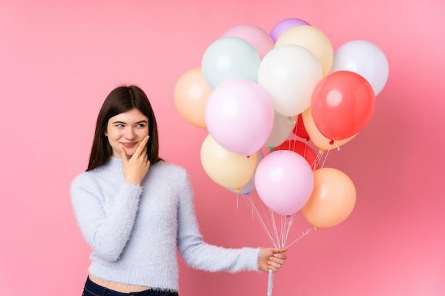Jong tienermeisje dat veel ballons over roze muur houdt denkend een idee