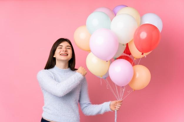 Jong tienermeisje dat veel ballons over roze muur houdt die een overwinning viert