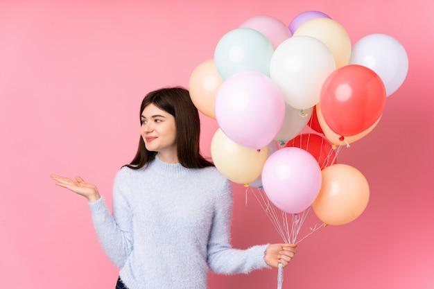 Jong tienermeisje dat veel ballons over roze muur houdt die lege ruimte op de palm houdt