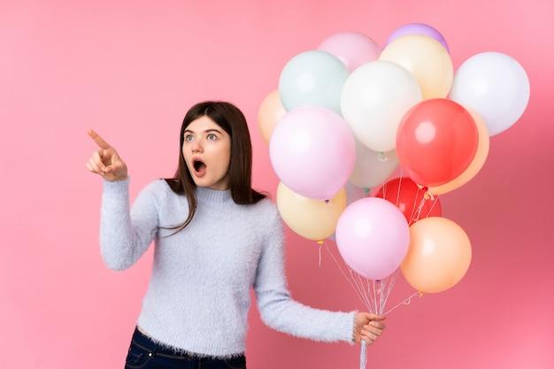 Jong tienermeisje dat veel ballons over roze muur houdt die weg richt