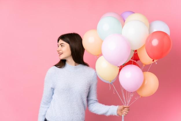 Jong tienermeisje dat veel ballons over roze muur houdt kijkend aan de kant