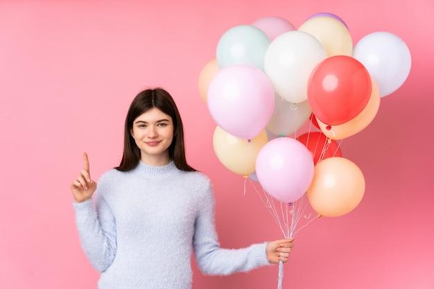 Jong tienermeisje dat veel ballons over roze muur houdt richtend met de wijsvinger een groot idee