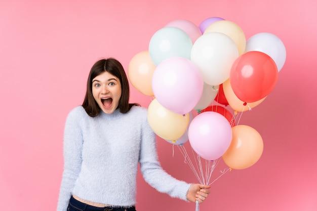 Jong tienermeisje dat veel ballons over roze muur met verraste gelaatsuitdrukking houdt