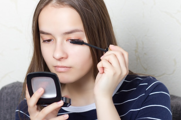 Jong tienermeisje doet een natuurlijke make-up voordat ze naar een feestje of een wandeling gaat, wenkbrauwen, wimpers schildert