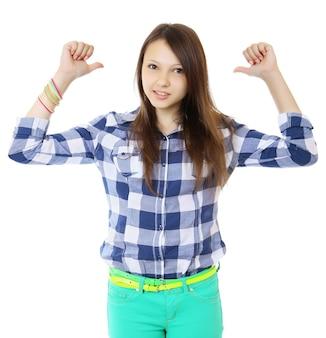 Jong tienermeisje in geruite overhemd wijst twee vinger achter zijn rug.