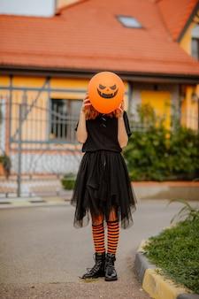 Jong tienermeisje in zwarte kleren die zich tegen oranje huis bevinden en halloween-ballon voor haar gezicht houden. vakantieconcept.