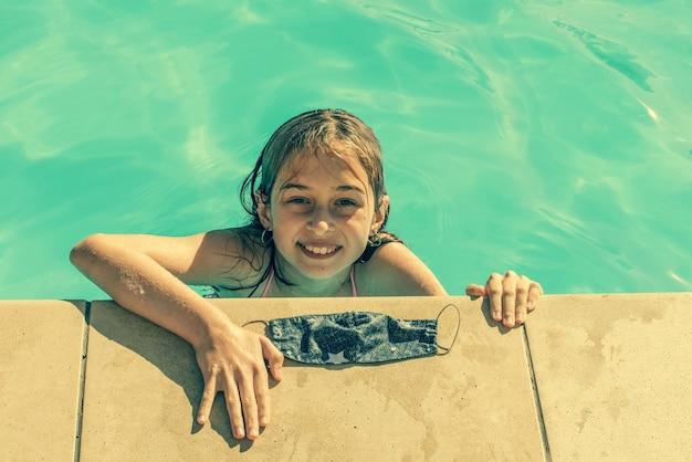 Jong tienermeisje met beschermend masker in het zwembad