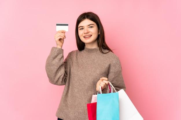 Jong tienermeisje over roze muurholding het winkelen zakken en een creditcard