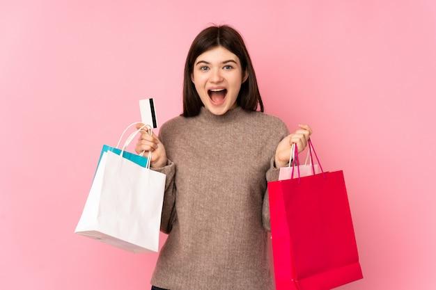 Jong tienermeisje over roze muurholding het winkelen zakken en verrast
