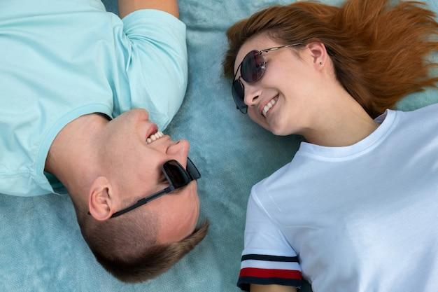 Jong tienerpaar die in zonnebril samen op blauwe doek leggen die liefde van relaties genieten.