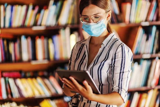 Jong toegewijd slim universiteitsmeisje met gezichtsmasker bij het houden van tablet en het hebben van externe klasse