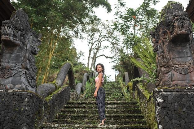 Jong toeristenmeisje die in camera op oude steenbalinesse treden blijven kijken