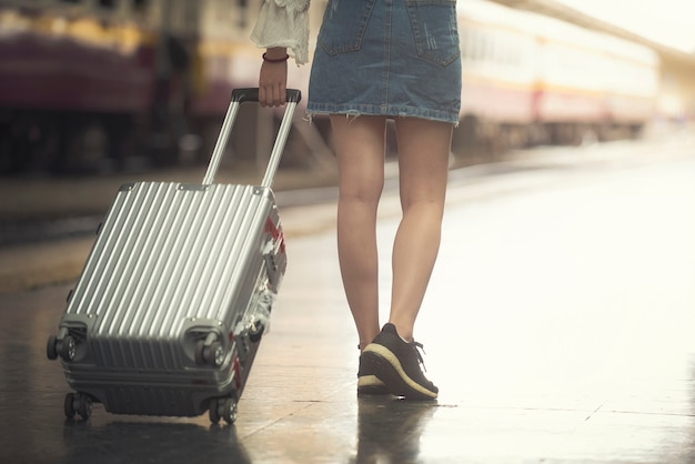 Jong toeristenmeisje die slepende bagage lopen die op station lopen