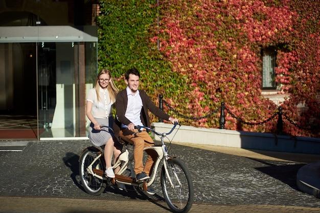 Jong toeristenpaar, man en vrouw die fiets achter elkaar fietsen langs grijze straat op heldere zonnige dag