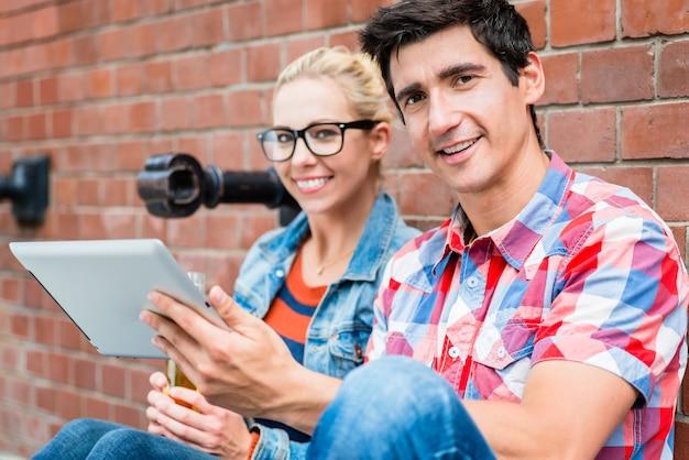 Jong toeristisch stel dat online stadsgids leest voordat ze een scootertour in berlijn maken