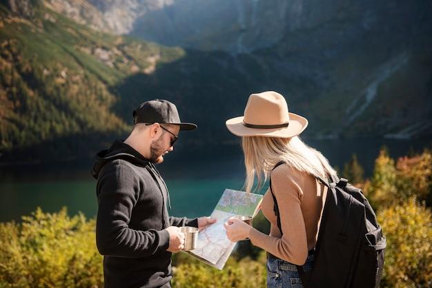 Jong toeristisch stel, man en vrouw, op wandelpad in bergen, kaart vasthoudend en weg vindend in de natuur op zonnige dag