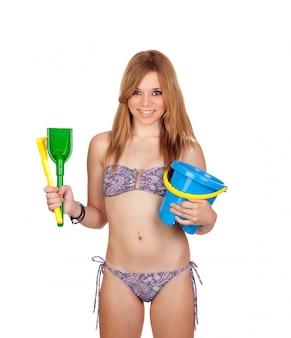 Jong toevallig meisje met bikini en speelgoed voor het strand dat op witte achtergrond wordt geïsoleerd