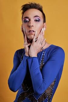 Jong transgender model met gele achtergrond een blauwe jurk