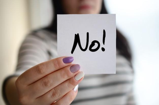 Jong triest meisje toont een witte sticker. kaukasische brunette die een vel papier met bericht. nee!