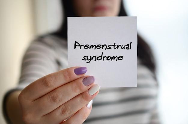 Jong triest meisje toont een witte sticker premenstrueel syndroom