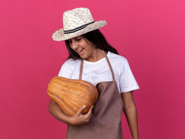 Jong tuinman meisje in schort en zomerhoed bedrijf pompoen kijken met glimlach op gezicht blij en opgewonden staande over roze muur