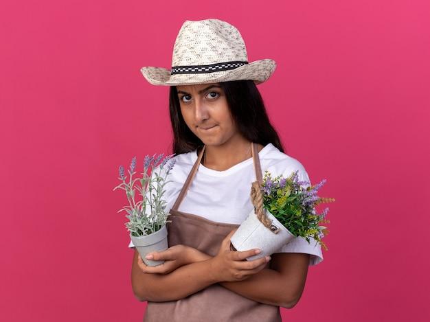 Jong tuinmanmeisje in schort en de zomerhoed die potplanten met boos gezicht houden die zich over roze muur bevinden