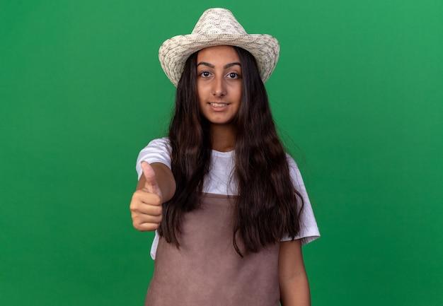Jong tuinmanmeisje in schort en de zomerhoed het glimlachen tonen duimen die omhoog zich over groene muur bevinden