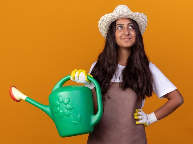 Jong tuinmanmeisje in schort en zomerhoed die gieter met glimlach op gezicht houden die zich over oranje muur bevinden