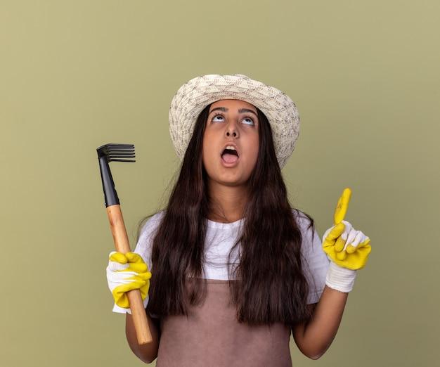 Jong tuinmanmeisje in schort en zomerhoed die werkhandschoenen dragen die minihark houden die omhoog wijzen met wijsvingers omhoog staand over groene muur kijken