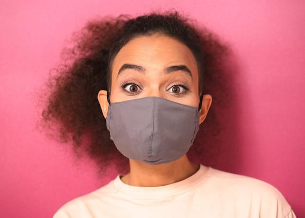 Jong uitziende geschokt afro-amerikaanse vrouw in licht peachy t-shirt in herbruikbaar gezichtsmasker