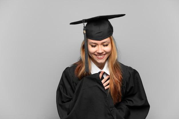 Jong universitair afgestudeerd meisje over geïsoleerde achtergrond lacht veel