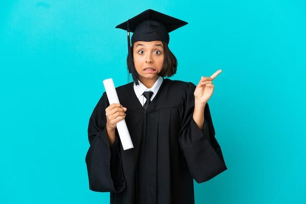 Jong universitair afgestudeerd meisje over geïsoleerde blauwe achtergrond bang en wijzend naar de zijkant
