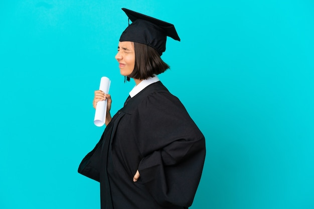 Jong universitair afgestudeerd meisje over geïsoleerde blauwe achtergrond die lijdt aan rugpijn omdat ze moeite heeft gedaan
