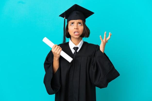 Jong universitair afgestudeerd meisje over geïsoleerde blauwe achtergrond gestrest overweldigd