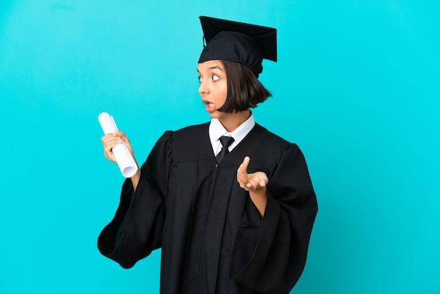 Jong universitair afgestudeerd meisje over geïsoleerde blauwe achtergrond met verrassingsuitdrukking terwijl ze opzij kijkt