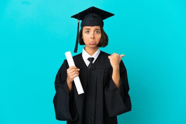 Jong universitair afgestudeerd meisje over geïsoleerde blauwe achtergrond ongelukkig en wijzend naar de zijkant