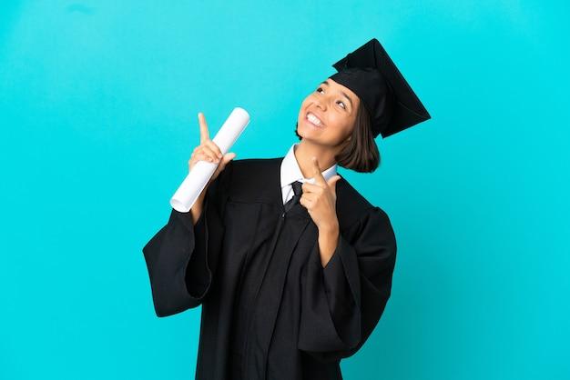 Jong universitair afgestudeerd meisje over geïsoleerde blauwe achtergrond wijzend met de wijsvinger een geweldig idee