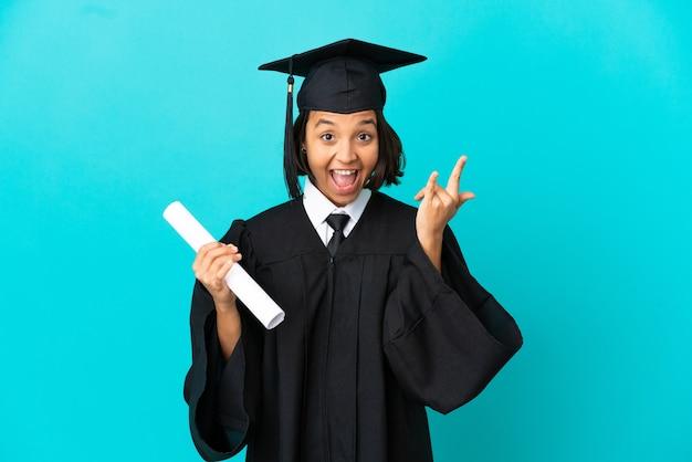 Jong universitair gediplomeerd meisje dat over geïsoleerde blauwe achtergrond hoorngebaar maakt
