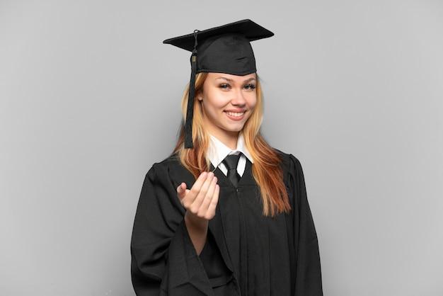 Jong universitair gediplomeerd meisje over geïsoleerde achtergrond die uitnodigt om met de hand te komen. blij dat je gekomen bent